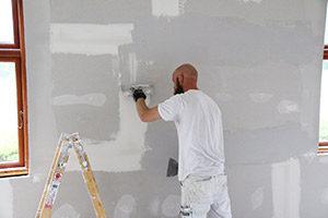 Maler i færd med spartling af gips