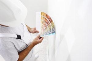 Maler vælger ny farve til hvid væg, ud fra farvepalette som holdes i hånden