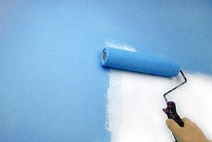 Hvid væg males lyseblå med malerrulle.