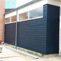 Træværk på tilbygning malet i mørk blå farve
