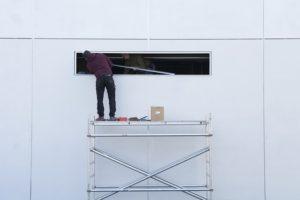 Mand på stillads i gang med at renovere hus